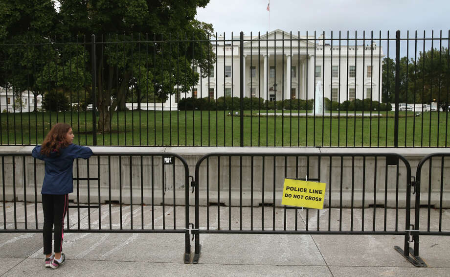 A young girl stands at a added security fence at the White House, where an intruder last week ran into the East Room. Photo: Mark Wilson / Getty Images / 2014 Getty Images