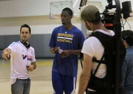 """Morgan Wise (left) directs Golden State Warriors forward Harrison Barnes during a video shoot at the team's training facility in Oakland, Calif. on Friday, Sept. 12, 2014, to promote """"One City"""", a new program organized by the San Francisco Citizens Initiative for Technology and Innovation."""