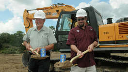 Chuck Fougeron, left, Vice-President of Southern Star Brewing Company, and his son, Dave, President, pose for photos during the groundbreaking ceremony for their brewing facility in Conroe on Monday.