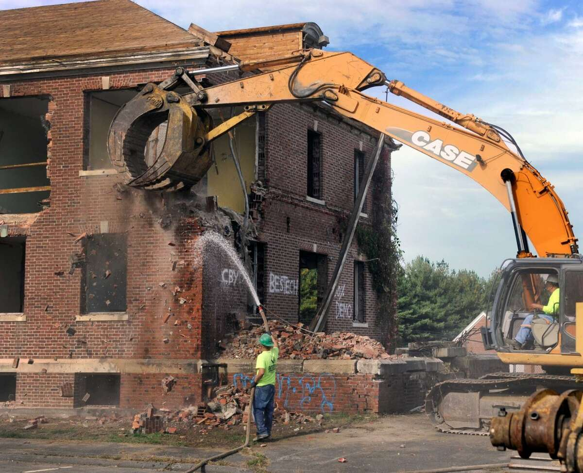 The demolition of Danbury Hall is underway at Fairfield Hills in Newtown, Conn. Julio Argueta keeps the water flowing to control the dust from the debris as an excavator run by Andy Bowolick, wacks the side of the building, Monday, Sept. 29, 2014.