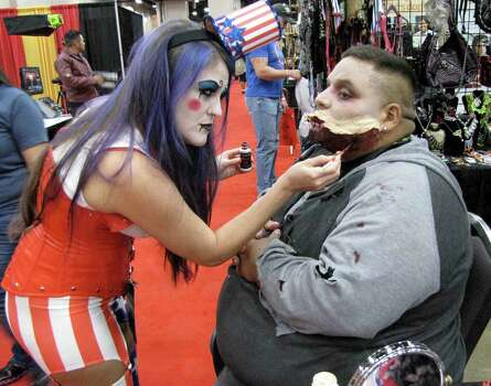 "Alyssa Mergele applies zombie makeup to Juan Escalante at the Starstruk booth during Alamo City Comic-Con Friday, Sept. 26, at Henry B. Gonzalez Convention Center. Starstuk, a local business, provides make-up and special effects for a variety of events. Escalante is in the cast of ""Zombie Reign,"" a zombie movie that will be filmed in the San Antonio area. Photo: Edmond Ortiz / S.A. Express-News"