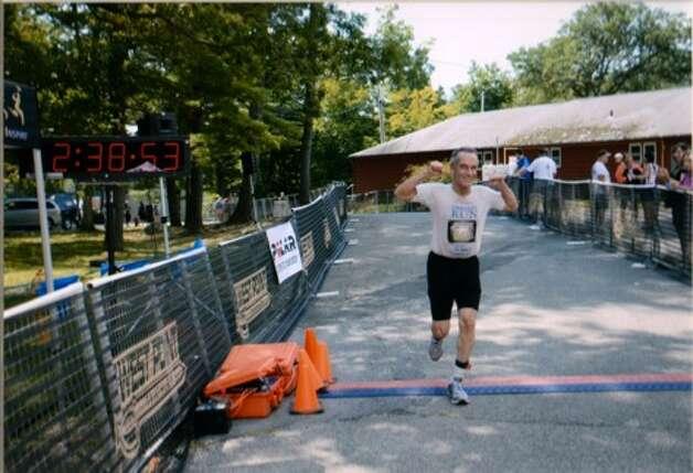 Robert Miller, 73, crosses the finish line at the West Point Triathlon. (Courtesy Robert Miller)