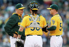 Young (left), talking with catcher Derek Norris and starting pitcher Sonny Gray,