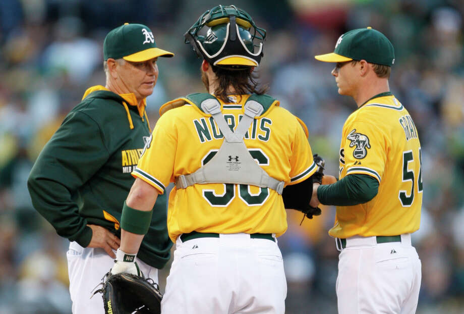 Young (left), talking with catcher Derek Norris and starting pitcher Sonny Gray, Photo: Michael Zagaris / Getty Images / ONLINE_CHECK