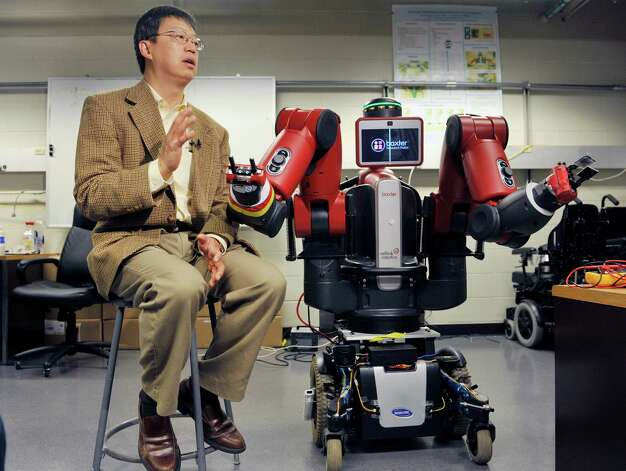 RPI professor, John Wen talks about Baxter, on right, an industrial robot mounted on a motorized wheelchair, at RPI in Troy, N.Y., during a media event to talk about the work being done on new technology to transform less expensive, human-friendly industrial robots into affordable assistive robots.    (Paul Buckowski / Times Union) Photo: Paul Buckowski / 10028801A