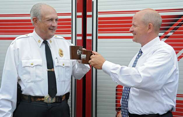 Albany Fire Department Chief Warren Abriel, left, toast with  Eric Stensland, Field Marketing Manager, Dunkin' Donuts after Dunkin' Donuts donates 100 pounds of coffee to the Albany Fire Department at the Brevator St. Fire Station on Monday Sept. 29, 2014 in Albany, N.Y. The donation was made on National Coffee Day where guests can walk into any participating Dunkin' Donuts restaurant in the Capital Region and receive a free medium cup of Dunkin' Donuts hot Dark Roast Coffee, with a limit of one per guest. (Lori Van Buren / Times Union) Photo: Lori Van Buren / 10028802A