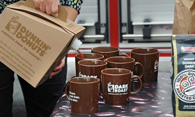 Hot dark roast coffee is poured into mugs at a press conference where Eric Stensland, Field Marketing Manager, Dunkin' Donuts donated 100 pounds of coffee to the Albany Fire Department at the Engine 10 Brevator St. Fire Station on Monday Sept. 29, 2014 in Albany, N.Y. The donation was made on National Coffee Day where guests can walk into any participating Dunkin' Donuts restaurant in the Capital Region and receive a free medium cup of Dunkin' Donuts hot Dark Roast Coffee, with a limit of one per guest. (Lori Van Buren / Times Union) Photo: Lori Van Buren / 10028802A