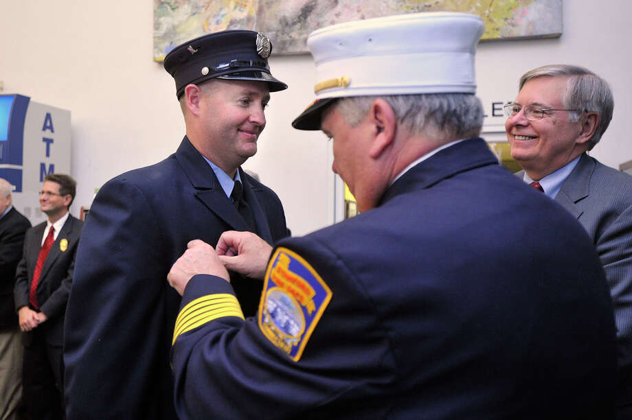 Firefighter Donald Lowndes, left, is awarded the 2014 Firefighter of the Year award from Fire Chief Peter Brown as Mayor David Martin looks on during the City of Stamford Fire Department 2014 Medal Day Ceremony at the Stamford Government Center in Stamford, Conn., on Monday, Sept. 29, 2014. Photo: Jason Rearick / Stamford Advocate