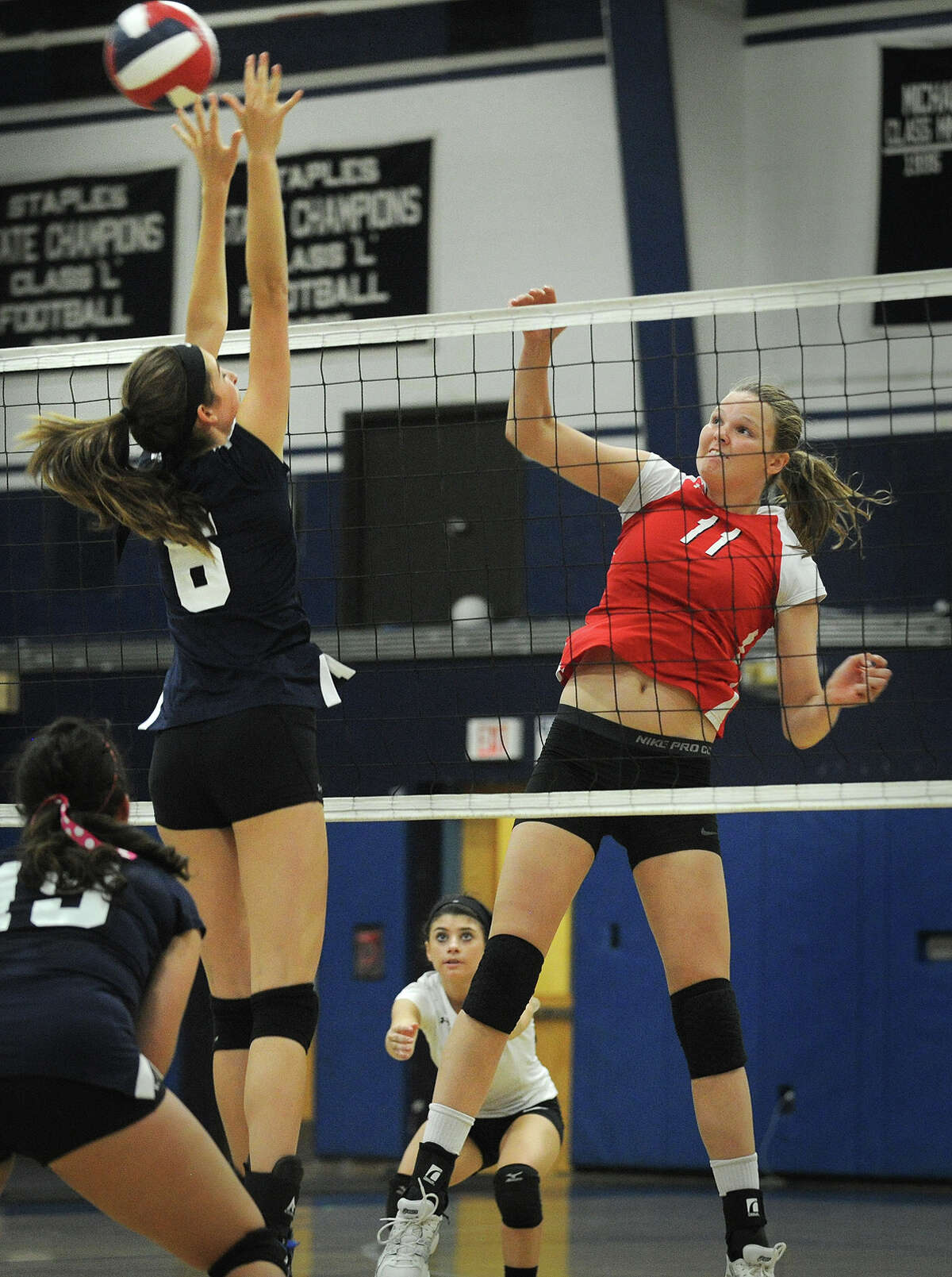 Greenwich's Abbie Wolf, right, spikes the ball off the block of Staples' Reece Schachne during their FCIAC girls volleyball match at Staples High School in Westport, Conn. on Monday, September 29, 2014.