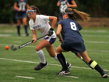 Westhill's Paige Sottosanti is pressured by Wilton's Kristen Godin during their field hockey game at Westhill High School in Stamford, Conn., on Monday, Sept. 29, 2014. Wilton won, 2-1.