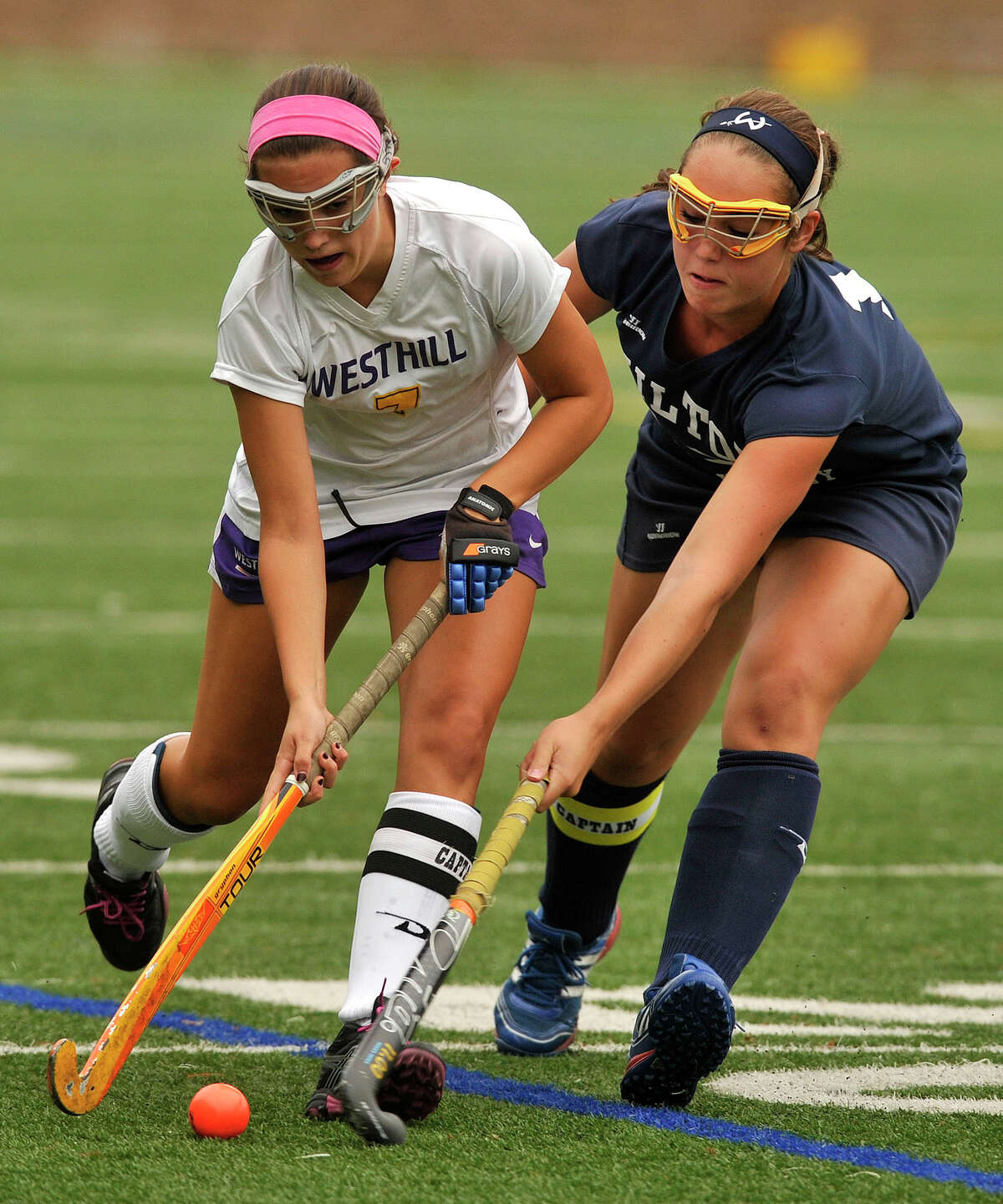 Westhill's Emma Hart is pressured by Wilton's Caroline Taverna during their field hockey game at Westhill High School in Stamford, Conn., on Monday, Sept. 29, 2014. Wilton won, 2-1.