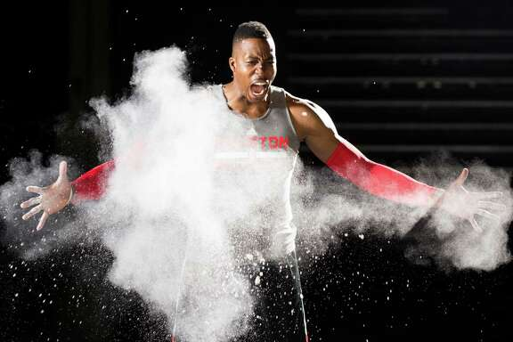 Center Dwight Howard channels his inner LeBron James with a star burst of powder as he shoots a video during Rockets media day at Toyota Center on Monday.