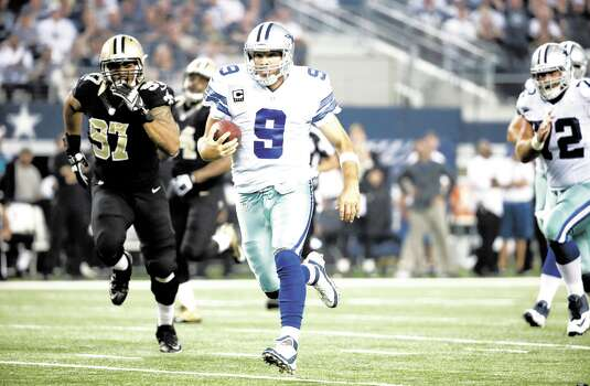 New Orleans Saints' Glenn Foster (97) gives chase as Dallas Cowboys quarterback Tony Romo (9) keeps the ball for a long run during the second half of an NFL football game, Sunday, Sept. 28, 2014, in Arlington, Texas. (AP Photo/Brandon Wade) Photo: Brandon Wade, Associated Press / FR168019 AP