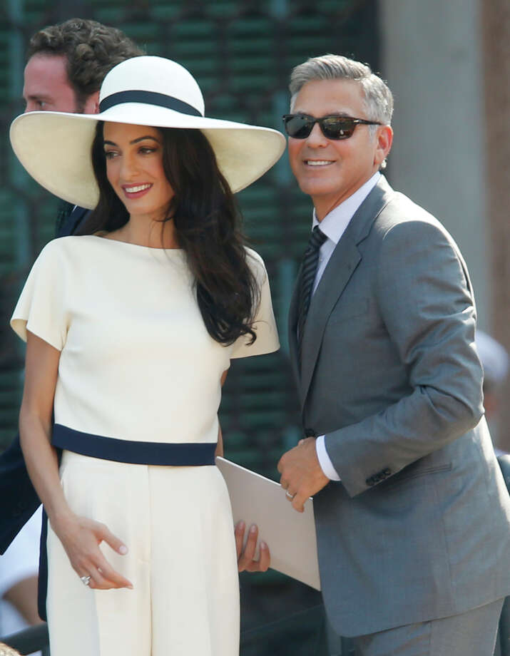 George Clooney, flanked by his wife Amal Alamuddin, arrives at the city hall for their civil marriage ceremony in Venice, Italy, Monday, Sept. 29, 2014. George Clooney married human rights lawyer Amal Alamuddin Saturday, the actor's representative said, out of sight of pursuing paparazzi and adoring crowds. (AP Photo/Luca Bruno) ORG XMIT: XLB109 Photo: Luca Bruno / AP
