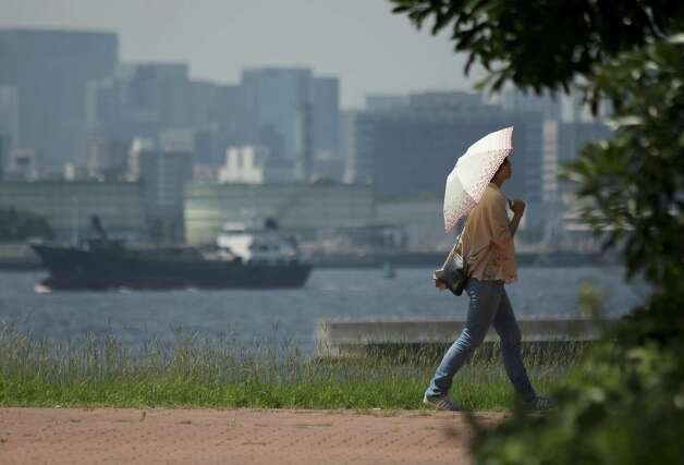 FILE - In this Aug. 20, 2014 file photo, a woman takes a walk under the scorching sun in Tokyo. Scientists looking at 16 cases of wild weather around the world last year see the fingerprints of man-made global warming on more than half of them. Researchers found that climate change increased the odds of nine extremes: Heat waves in Australia, Europe, China, Japan and Korea, intense rain in parts of the United States and India, and severe droughts in California and New Zealand.  (AP Photo/Eugene Hoshiko, File) ORG XMIT: WX102 Photo: Eugene Hoshiko / AP