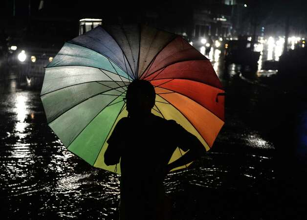 A pedestrian stands with an umbrella as rain falls in Bangalore on August 14, 2013. The monsoon season, which runs from June to September, accounts for about 80 percent of India's annual rainfall, vital for a farm economy which lacks adequate irrigation facilities. However, the flooding also causes hundreds of deaths and damage to infrastructure, homes and farms across India. AFP PHOTO/Manjunath KIRANManjunath Kiran/AFP/Getty Images Photo: MANJUNATH KIRAN / AFP