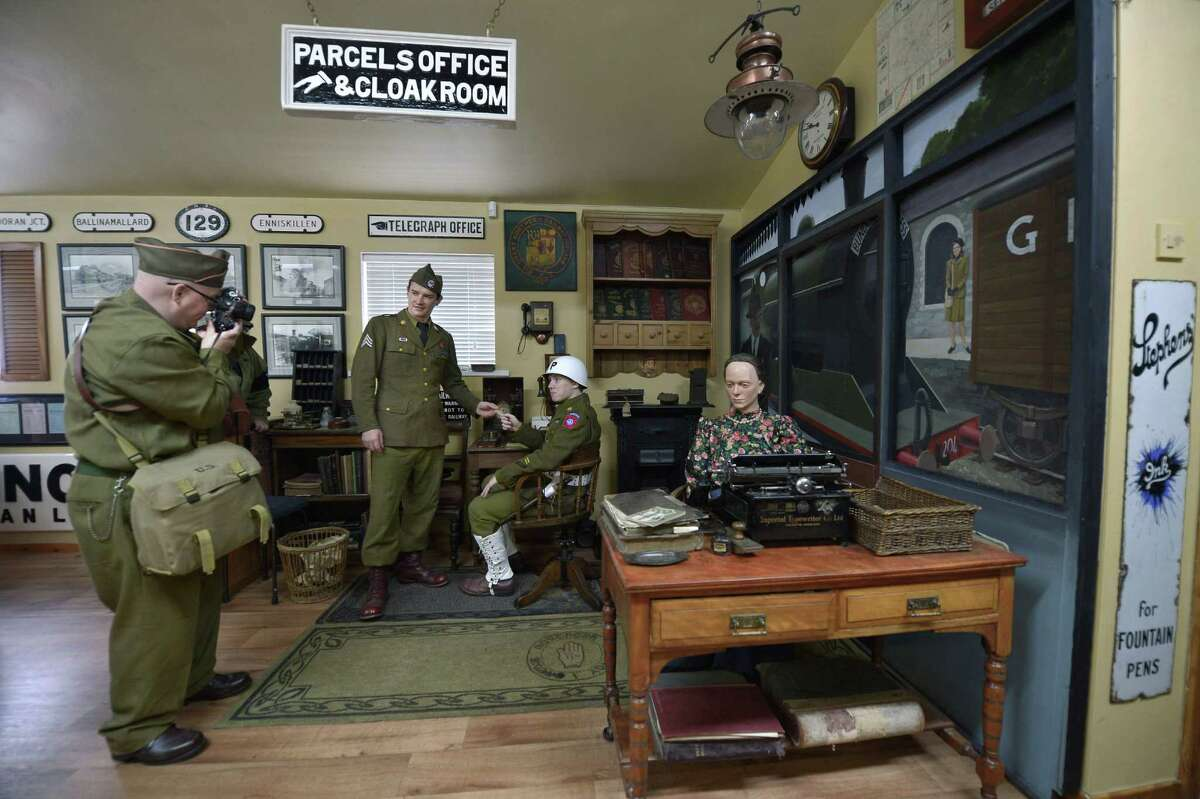 A group of men from the Wartime Living History Association dressed as American G.I's take photographs of one another in the waiting room of the Headhunters Barber Shop and Railway Museum on September 29, 2014 in Enniskillen, Northern Ireland.