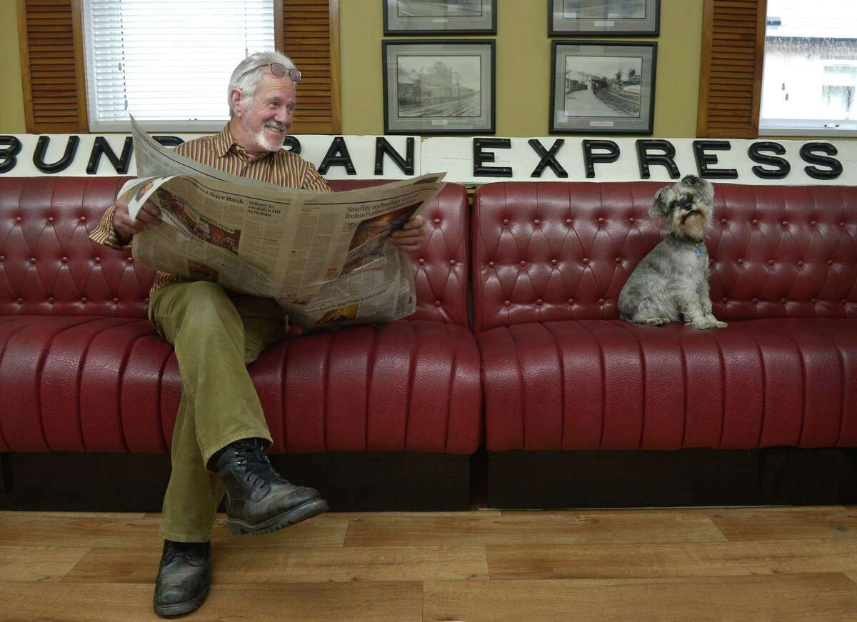 Roxy, the 'station dog' watches proceedings from the waiting room couch beside Andrew Brennan at the Headhunters Barber Shop and Railway Museum on September 29, 2014 in Enniskillen, Northern Ireland.