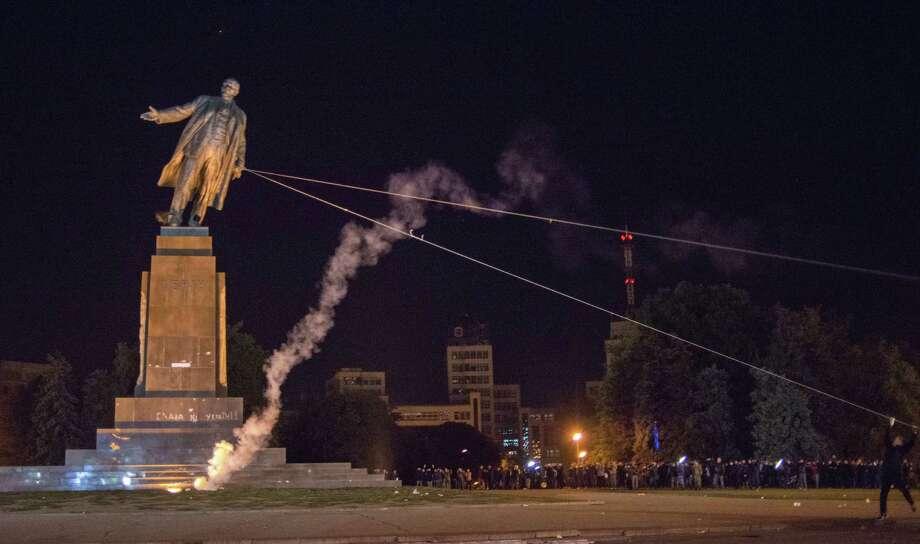 A monument to Vladimir Lenin falls Sunday in Kharkiv, Ukraine. Other Lenin statues also have fallen amid anti-Russia sentiment. Photo: Igor Chekachkov / Associated Press / AP