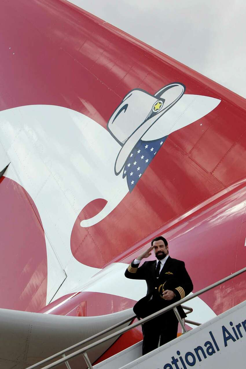 Actor John Travolta salutes from air stairs positioned next to a Qantas A380 at Dallas-Fort Worth Airport in Texas on Monday, Sept. 29, 2014. Travolta, Qantas' Good Will Ambassador, was on hand as the airline celebrated the A380's inaugural arrival at the airport.