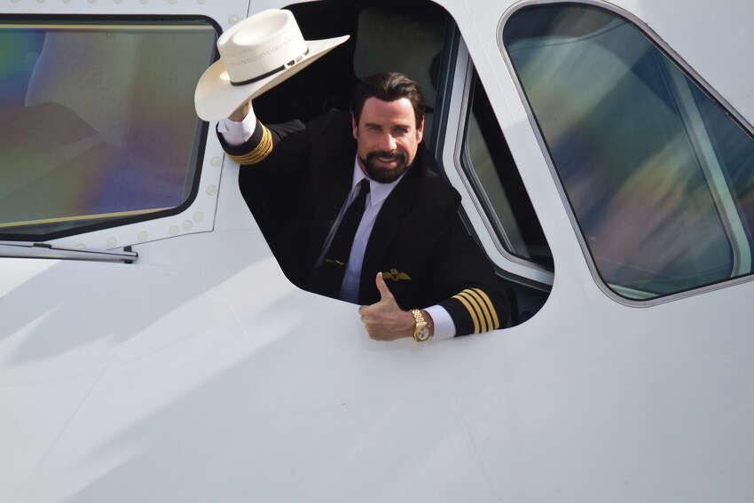Actor John Travolta salutes in a Qantas A380 service from Dallas-Fort Worth in Texas to Sydney on Monday.