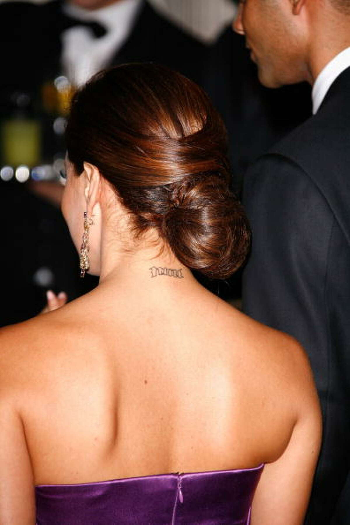 PARIS - SEPTEMBER 21: A tattoo on Eva Longoria's neck is seen as she arrives at the 'Par Coeur Gala' at Hotel Meurice on September 21, 2009 in Paris, France. (Photo by Julien Hekimian/WireImage)
