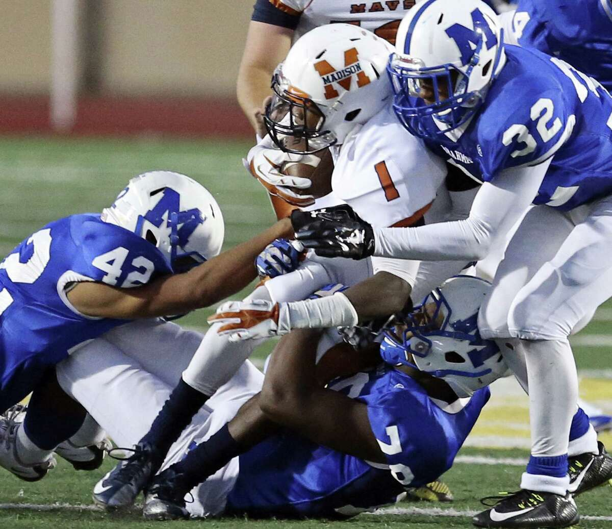 Madison's Alex Ardoin is gang tackled by MacArthur's Sergio Herrera (from left), Xavier Bryant and Deandre Frowner during first half action Sept. 27at Comalander Stadium. MacArthur beat Madison for the first time since 2010, 43-27.