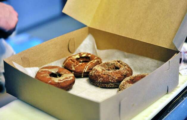 Various donuts are placed in a box to fill a customer's order at Nibble Inc., a donut shop at the corner of Fifth Ave and Broadway, in Troy, N.Y. on Tuesday, Sept. 30, 2014.  (Paul Buckowski / Times Union) Photo: Paul Buckowski / 10028818A