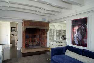 The living room hosts a grand, chateau-style fireplace.