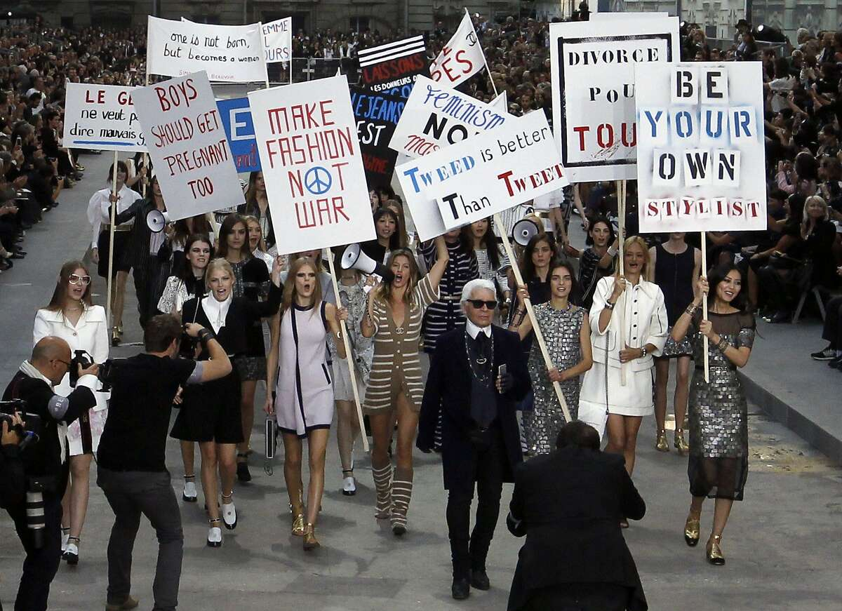 Higher wages for higher cheekbones! Designer Karl Lagerfeld and Gisele Bündchen (in stripes) lead models in a fake protest demanding, among other things, male pregnancy and the wearing of tweed at Chanel's Spring/Summer 2015 ready-to-wear fashion collection in Paris. They were not pepper-sprayed - unfortunately.