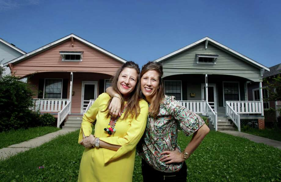 Identical twins Dana Smidt, left, and Jana Smidt,  right, pose in front of the look-alike houses they recently bought in Galveston shown Tuesday, Sept. 30, 2014. (Melissa Phillip / Houston Chronicle) Photo: Melissa Phillip, Houston Chronicle / © 2014  Houston Chronicle