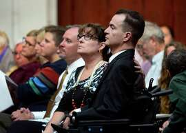 Brandon Coats, a quadriplegic medical marijuana patient who was fired by the Dish Network after failing a drug test more than four years ago, right, waits for the proceedings to begin with his mother, Donna Scharfenberg, at the Colorado Supreme Court in Denver on Tuesday, Sept. 30, 2014. Coats' case highlights the clash between state laws that are increasingly accepting of marijuana use and employers' drug-free policies that won't tolerate it.