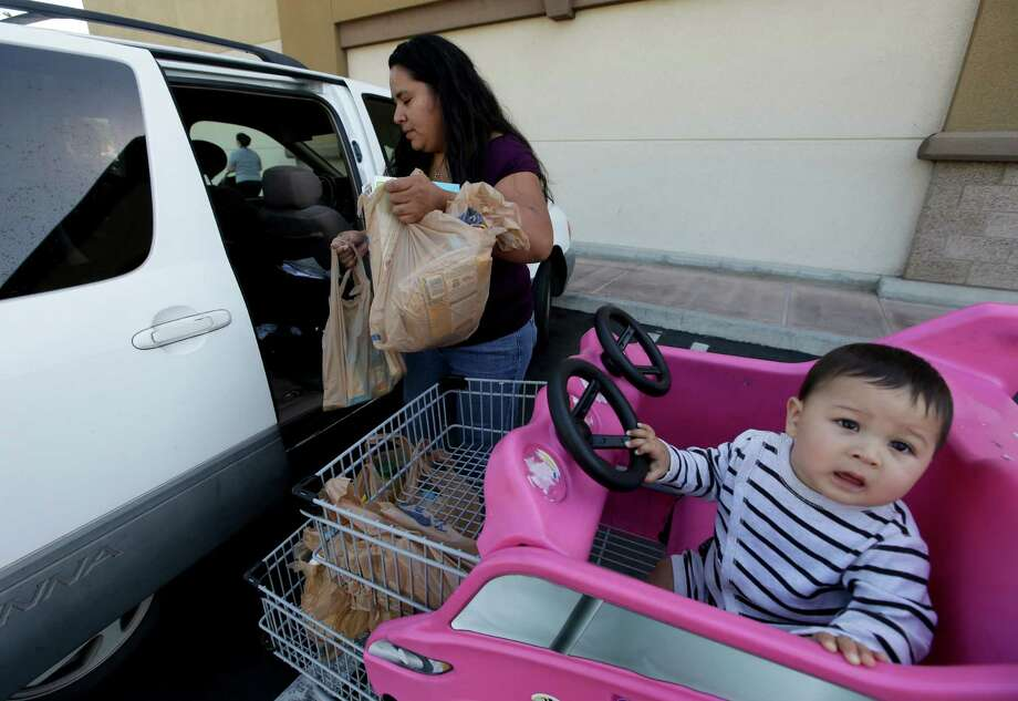 Irma Salazar, left, of Santa Ana, Calif., loads plastic grocery bags into her car as her son Miguel looks on, Tuesday, Sept. 30, 2014 in Santa Ana, Calif. Gov. Jerry Brown has signed legislation on Tuesday imposing the nation's first statewide ban on single-use plastic bags.(AP Photo/Chris Carlson) Photo: Chris Carlson, STF / AP