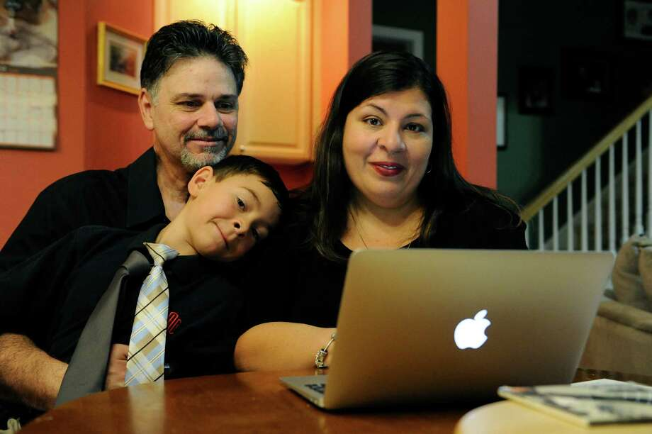 Marisela Martinez-Cola, right, a lawyer and a parent living in an Atlanta suburb with her husband Greg, left, and their 7-year-old son, David, pose for photos as they prepare for a typical school and work day Tuesday, Sept. 30, 2014, in Lawrenceville, Ga. The couple send their son to private school and have hired a tutor to improve David's reading _ expenses made possible by Greg's salary as a regional buyer for Costco Wholesale. (AP Photo/David Tulis) Photo: David Tulis, FRE / FR170493 AP