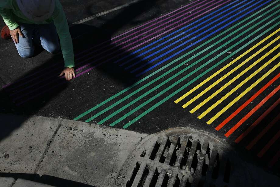 Click through this gallery for a look at the creation of Castro's rainbow sidewalk. Donald Bowman with Asphalt Impressions works on installing a new rainbow crosswalk on the intersection of 18th and Castro Sept. 30, 2014 in San Francisco, Calif. The new rainbow crosswalks are part of  a two-block street redesign in the Castro with the Department of Public Works. Photo: Leah Millis, The Chronicle