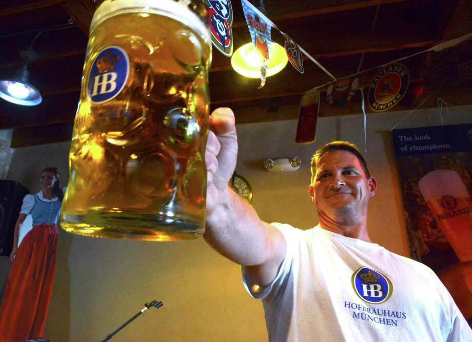 Jason Hurta of New Braunfels is the national champion of  Masskrugstemmen, a German sport in which contestants hold with extended arm a 1-liter stein filled with beer for as long as possible. Sept. 26, 2014. Photo: San Antonio Express-News / San Antonio Express-News