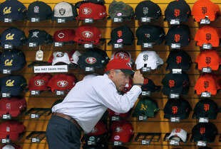 A customer tries on a 49ers cap at Lombardi Sports. The family-owned Russian Hill store will close in January after 66 years in business.  in San Francisco, Calif. on Tuesday, Sept. 30, 2014. The popular, family-owned sporting goods store announced last week that it will be closing after 66-years in business. Supervisor David Campos plans to introduce legislation to create a registry of legacy businesses in the city.
