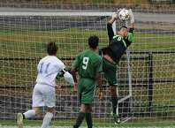 New Milford goalie Adam Llerena (0) jumps to make a save in New Milford's 4-0 win over Newtown in the high school soccer game at Treadwell Town Park in Sandy Hook, Conn. Tuesday, Sept. 30, 2014.