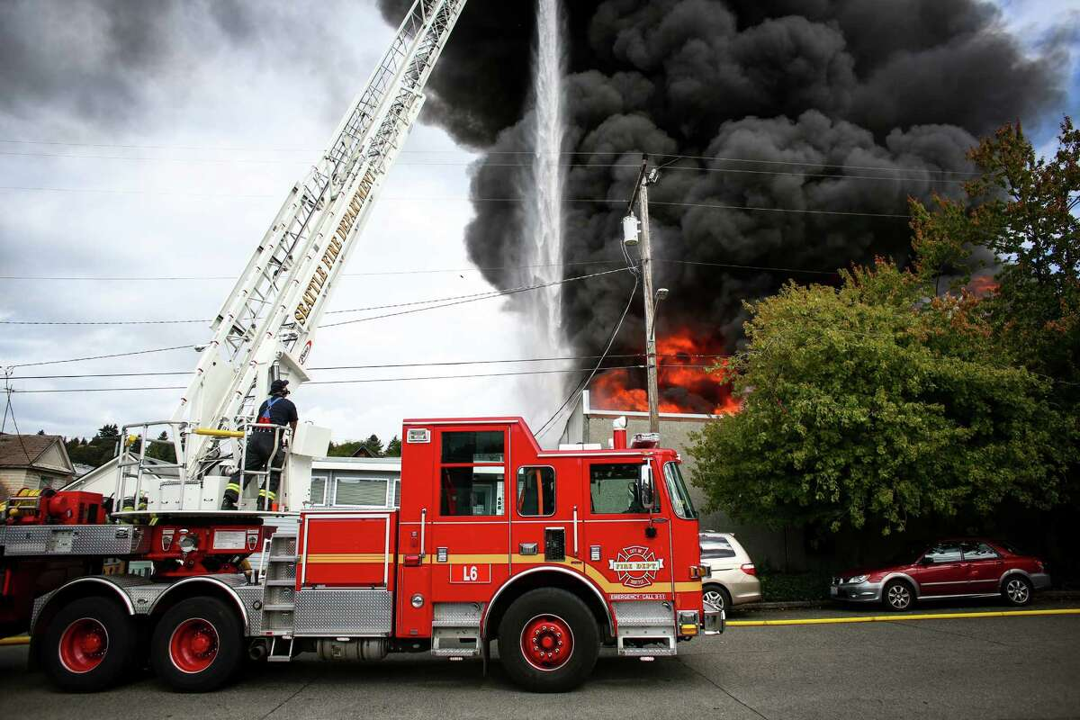 Firefighters work to control a large fire as ASKO Processing Inc., a metal-finishing company, burns in the heart of the Fremont neighborhood on Tuesday, September 30, 2014. The two-alarm fire completely destroyed the business and sent towering flames into the sky.