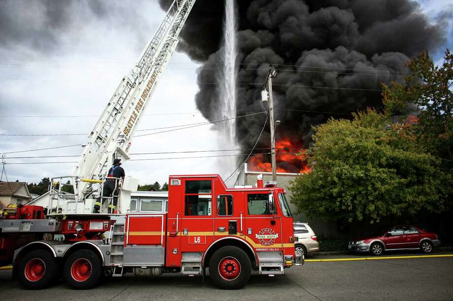 Firefighters work to control a large fire as ASKO Processing Inc., a metal-finishing company, burns in the heart of the Fremont neighborhood on Tuesday, September 30, 2014. The two-alarm fire completely destroyed the business and sent towering flames into the sky. Photo: JOSHUA TRUJILLO, SEATTLEPI.COM / SEATTLEPI.COM