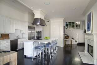 The expansive kitchen hosts a breakfast bar, stainless steel appliances and white cabinets.