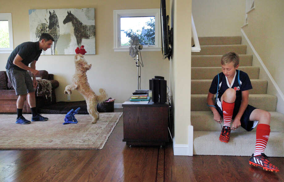 Chris Ford plays with Ozzie as his son Cole, 13, laces up his soccer cleats Sunday in their Mill Valley home. Photo: Leah Millis / The Chronicle / ONLINE_YES