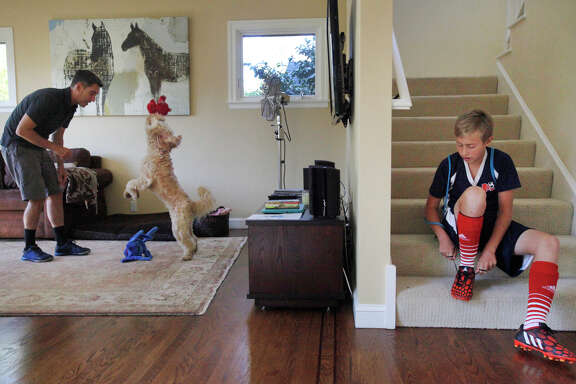 Chris Ford plays with Ozzie as his son Cole, 13, laces up his soccer cleats Sunday in their Mill Valley home.