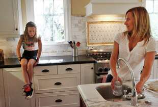 Leslie Ford negotiates evening activities with her daughter Cameran, 10, in the kitchen at their home Sept. 28, 2014 in Mill Valley, Calif. Chris Ford is self-employed and enrolled his family in Covered California last year. Since then, he has run into a few issues, including a bill in July for a backlog of bills from half the year from when the company hadn't been utilizing the automatic payment method Chris signed up for. He says he's also been running into to trouble finding a doctor.