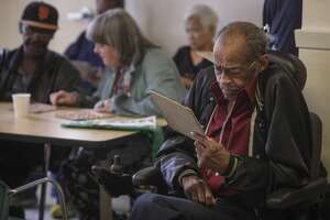 Norbert Charles partakes in a game of Bingo run by volunteers from the software startup Zendesk at the Curry Senior Center in the Tenderloin on September 24th 2014. A rotating group of companies volunteer at the senior center each week.