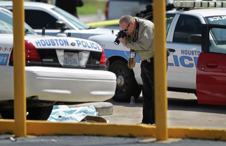 An investigator takes photos of an unidentified male suspect after he was shot dead by a Houston police officer about 10:40 a.m. in the parking lot of Visionworks at 19210 Gulf Freeway near Bay Area Boulevard and Baybrook Mall according to the Houston Police Department Tuesday, Sept. 30, 2014, in Friendswood, Texas. ( Gary Coronado / Houston Chronicle ) Photo: Gary Coronado, Staff / © 2014 Houston Chronicle