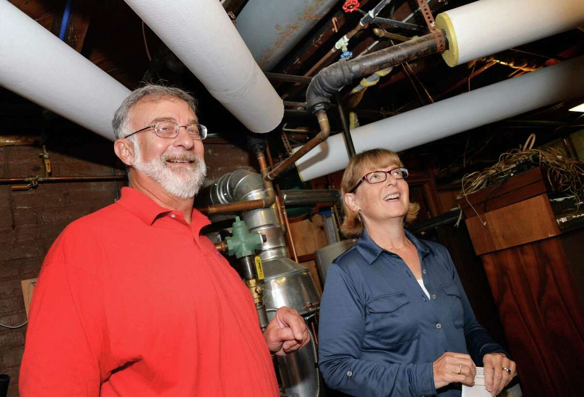 Richard Hartt and his wife Julie MacDonald describe how they insulated the furnace pipes in the basement of their North Lake Ave. home during a National Grid home heating news conference Tuesday Sept. 30, 2014, in Troy, NY. (John Carl D'Annibale / Times Union)