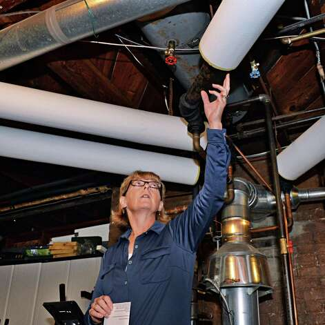 Home owner Julie MacDonald describes how she installed insulatation on the furnace pipes in the basement of her North Lake Ave. home during a National Grid home heating news conference Tuesday Sept. 30, 2014, in Troy, NY.   (John Carl D'Annibale / Times Union) Photo: John Carl D'Annibale / 10028816A