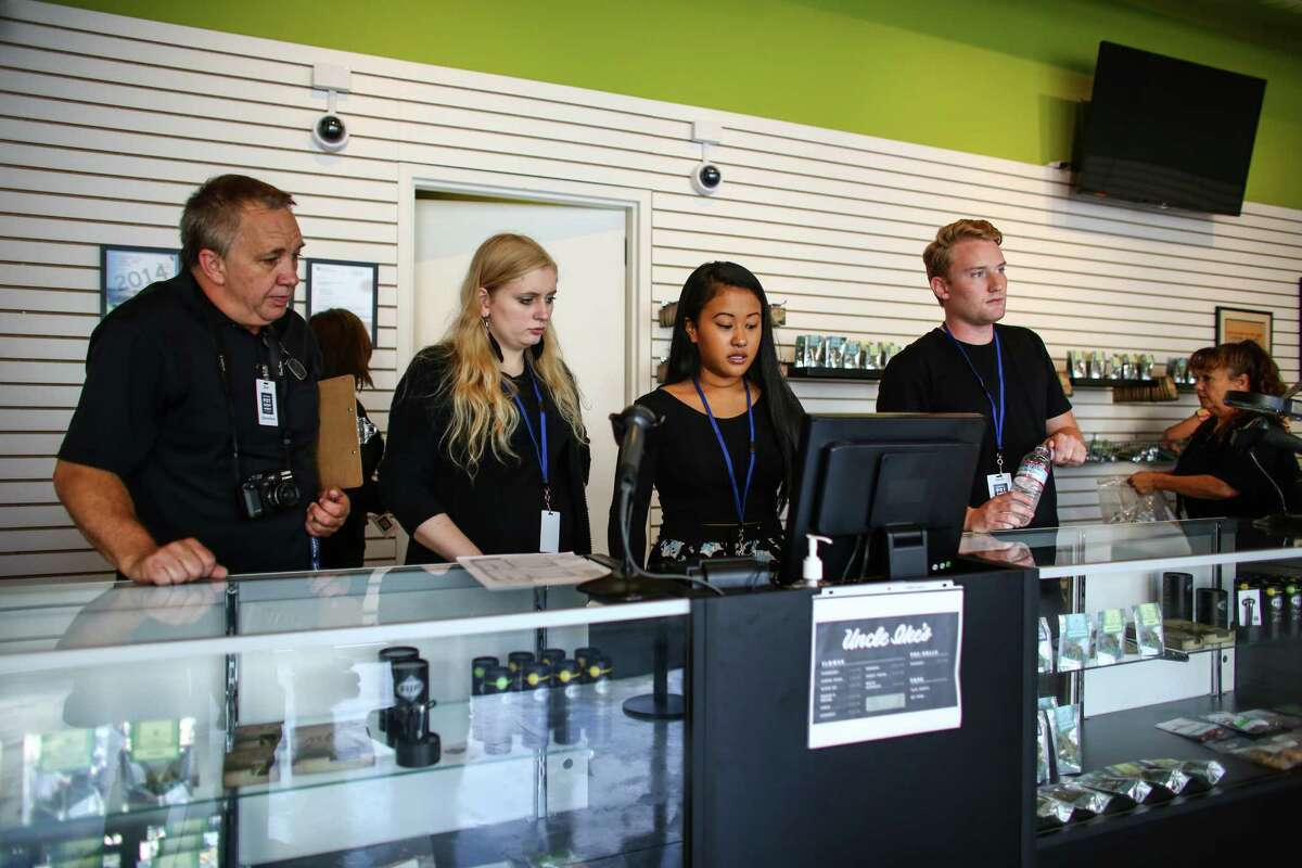 Employees wait for their first customers during the opening of Uncle Ike's Pot Shop at 23rd Avenue and East Union Street in Seattle on Tuesday, Sept. 30, 2014. The shop was the second recreational marijuana shop to open in Seattle.