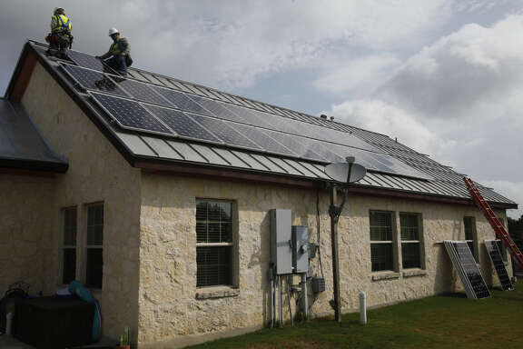Two Texas Solar Power-San Antonio workers install a 10.2-kilowatt system on the roof of a home near Boerne in 2012.